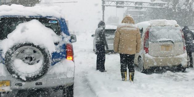 大雪で動けなくなった乗用車とドライバーら=6日午前、福井市内の国道8号 ※車のナンバーにモザイクをかけてあります 撮影日:2018年02月06日