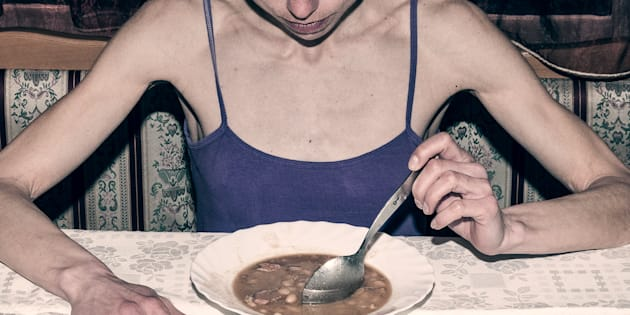 Anorexia. Skinny anorexic girl holding a spoon and look at the plate with food.