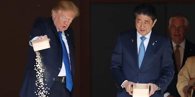 豪快にコイの餌を落とすトランプ大統領(左)と安倍首相