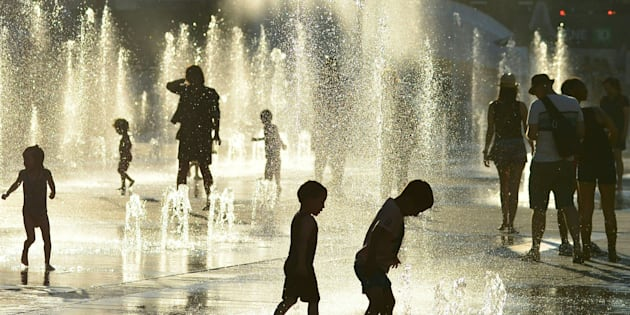 Children play in the water fountains at the Place des Arts in Montreal on a hot summer day July 3, 2018.