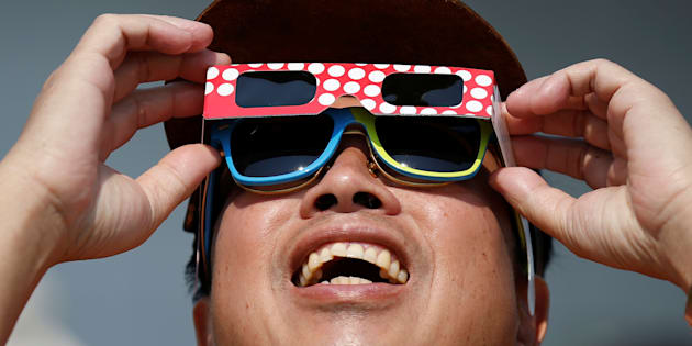 A man watches a partial solar eclipse at the Canada Aviation and Space Museum in Ottawa Aug. 21, 2017.