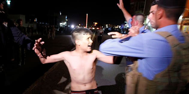 Iraqi security forces detain a boy after removing a suicide vest from him in Kirkuk, Iraq, Aug. 21, 2016.