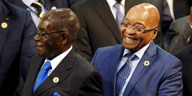 Zimbabwe President Robert Mugabe (L) reacts next to South Africa's President Jacob Zuma during the opening of the 25th African Union summit in Johannesburg, June 14, 2015.