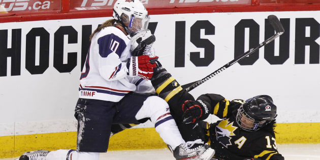 Canada's Caroline Ouellette crashes into Julie Chu of the U.S. during the first period of their preliminary round game at the IIHF Ice Hockey Women's World Championship in Ottawa on April 2, 2013.