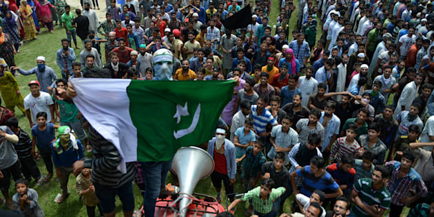 A masked Kashmiri mourner holds up a Pakistani flag in Budgam district on August 16, 2016.