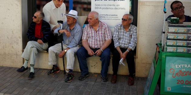 Un grupo de pensionistas sentados delante de una oficina del BBVA en Málaga.