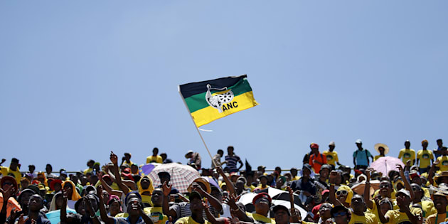 Supporters of the African National Congress (ANC) wave a party flag during the party's 104th anniversary celebrations in Rustenburg, South Africa January 9, 2016. REUTERS/Siphiwe Sibeko      TPX IMAGES OF THE DAY