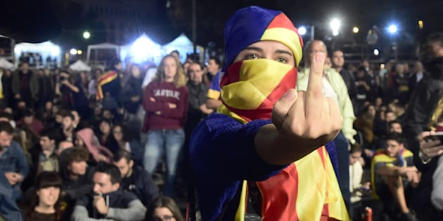 A woman, whose face is covered with a Catalan pro-independence flag, gestures as people sit on Plaza Catalunya square in Barcelona waiting for polls results after the closing of polling stations on October 1, 2017.  / AFP PHOTO / JOSE JORDAN        (Photo credit should read JOSE JORDAN/AFP/Getty Images)
