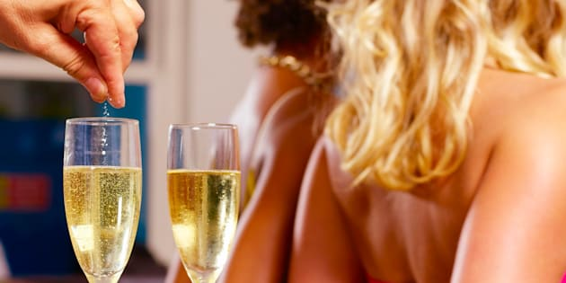 Man spiking girls champagne drinks in bar
