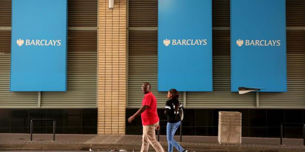 A couple walks past a Barclays logo in Johannesburg.