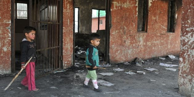 Small children play at the burnt building of government school at Gori Pora on October 31, 2016 in Srinagar, India.