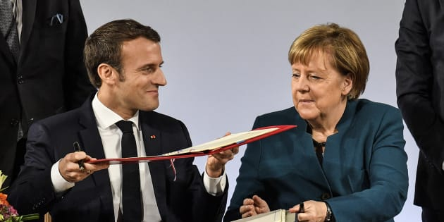 German chancellor Angela Merkel, right, and French President Emmanuel Macron, left, change documents during the signing of the new Germany-France friendship treaty at the historic Town Hall in Aachen, Germany, Tuesday, Jan. 22, 2019. The new Treaty of Aachen is the succession of the 1963 Elysee Treaty signed by West German Chancellor Konrad Adenauer and the then French President Charles de Gaulle. (AP Photo/Martin Meissner)
