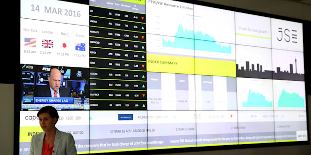 A television presenter speaks in front of a reception with an electronic board displaying movements in major indices at the Johannesburg Stock Exchange building in Sandton Johannesburg, March 14, 2016.