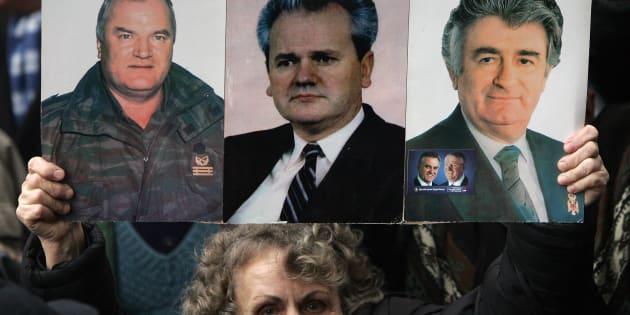 Una mujer serbia muestra la imagen del General Ratko Mladic (L), de Slobodan Milosevic (C) y de Radovan Karadzic durante una protesta en Belgrado, en febrero de 2007.