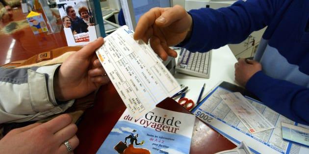 Un employé de la SNCF délivre un billet de train à son guichet.