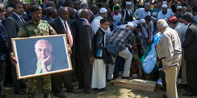 Helpers place the body of late South African anti-apartheid activist Ahmed Kathrada in the grave as South African ruling party African National Congress (ANC) leadership, political opposition leaders, dignitaries and family members attend the funeral at the Westpark Cemetery in Johannesburg, South Africa, on March 29, 2017. The funeral of celebrated South African anti-apartheid activist Kathrada was transformed into a rally against President Jacob Zuma, who did not attend after the family of the ANC stalwart, one of Nelson Mandela's closest colleagues in the struggle against white minority rule who died on March 28, 2017 aged 87, had asked Zuma to stay away.