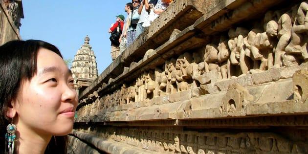 A tourist admires the erotic sculptures at the Khajuraho temple during the week-long annual dance festival in Khajuraho February 26, 2006. REUTERS/Raj Patidar