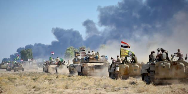 Fuerzas chiítas y soldados de Irak accediendo, ayer, a Al Hauiya.