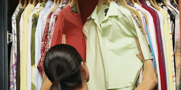 Young woman choosing clothes from wardrobe, rear view