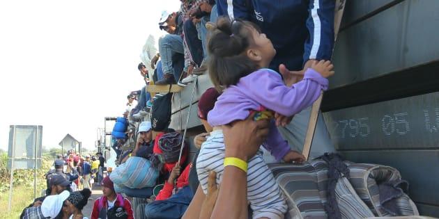 Un migrante entrega a una niña menor de 3 años a otro migrante que se dirige hacia la frontera norte de México