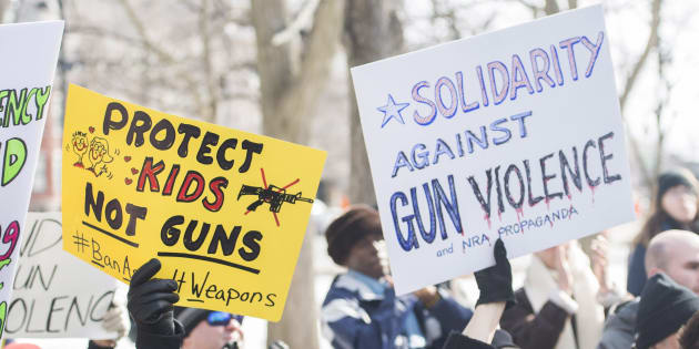 People hold up signs during a 'March for Our Lives' rally to show solidarity with the U.S. gun control movement in Montreal on Saturday.