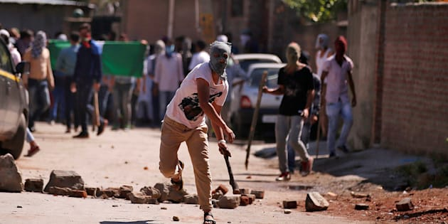 A demonstrator hurls a stone during a protest in Srinagar against the recent killings in Kashmir.