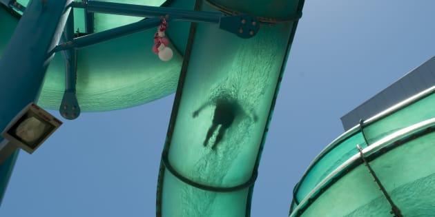 Un niño se tira por el tobogán en un parque acuático, en una imagen de recurso.