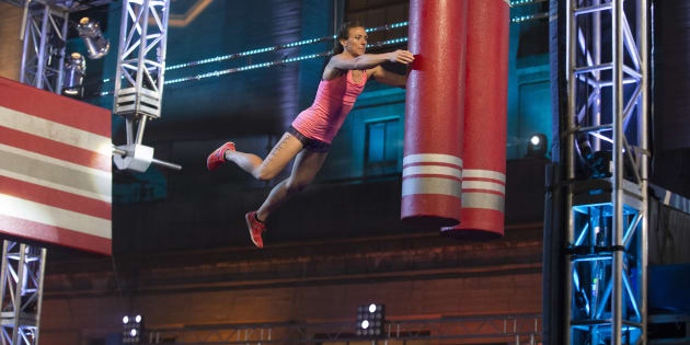 An American Ninja Warrior contestant jumps and hopes.