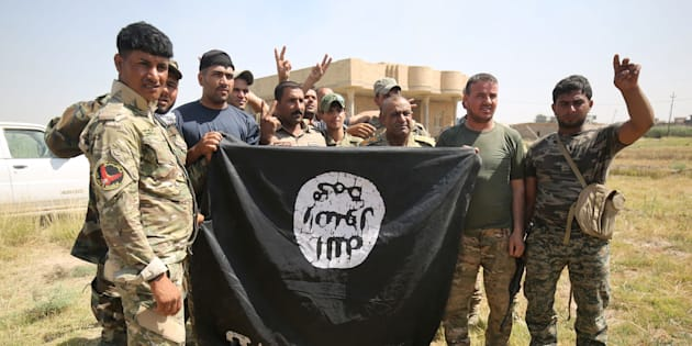 Iraqi Shiite fighters from a Popular Mobilisation unit hold an Islamic State (IS) group flag in an operation in al-Shahabi village, east of Fallujah, to retake the city from (IS) jihadists, on May 24, 2016. Iraqi forces cleared areas around Fallujah on May 24 after launching an assault to retake the city, tightening their siege on Islamic State group fighters. With the jihadists surrounded and outnumbered, the recapture of their iconic bastion looked ultimately inevitable, especially after IS suffered a string of losses in recent months. / AFP / AHMAD AL-RUBAYE        (Photo credit should read AHMAD AL-RUBAYE/AFP/Getty Images)
