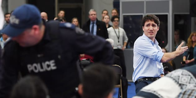 Prime Minister Justin Trudeau argues with a protester as police officers intervene at a public town hall in Nanaimo, B.C. on Feb. 2, 2018.