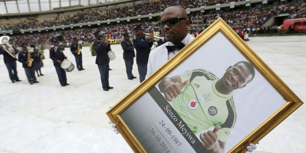 A man holds a framed picture of  South African national soccer team goalkeeper and captain, Senzo Meyiwa during his funeral service in Durban on November 1, 2014.