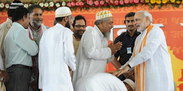 Indian Muslims greetNarendra Modi (R) at the Gujarat University Convention Centre in Ahmedabad on September 17, 2011.