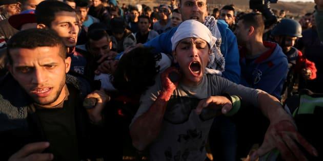 Un palestino herido es trasladado por otros manifestantes tras concentrarse ante soldados de Israel en la frontera de Gaza.