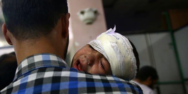Un hombre consuela a un niño herido en un bombardeo en zona rebelde de Douma, en pasado diciembre.