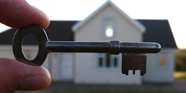 A house key held in front of a house, as all houses put up for sale must have a home report carried out.