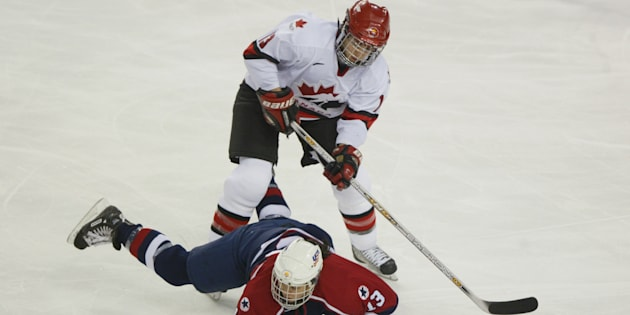 Caroline Ouellette of Canada knocks down Julie Chu of the U.S. during the women's ice hockey gold medal game on Feb. 21, 2002 at the Salt Lake City Winter Olympics.