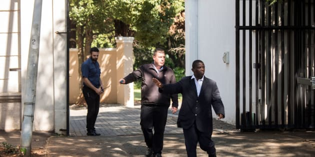 Private Security agents gesture as they stand guard outside the compound of the controversial business family Gupta in Johannesburg, on February 14, 2018.