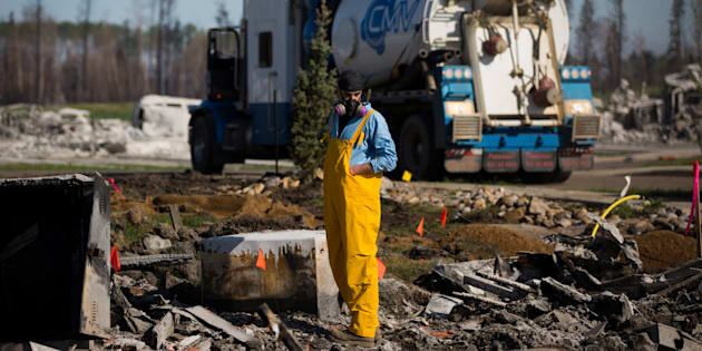 A resident looks over the damage in the Timberlea neighbourhood as thousands of evacuees who fled a massive wildfire begin to trickle back to their homes in Fort McMurray, Alta. on June 2, 2016.