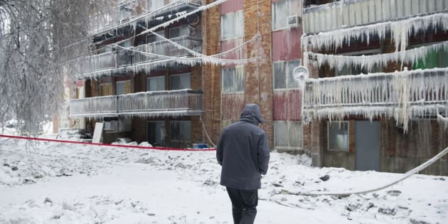 A man walks by a apartment complex destroyed by a fire in Longueuil, Que. on Jan. 16, 2018.