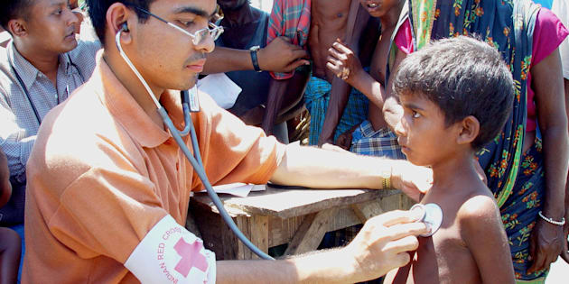 An Indian Red Cross doctor attends to a patient on the river island Tupka Chaar in the northeastern Indian state of Assam July 24, 2003.