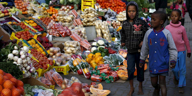 Children walk past a vegetable stall in Soweto July 23, 2015.