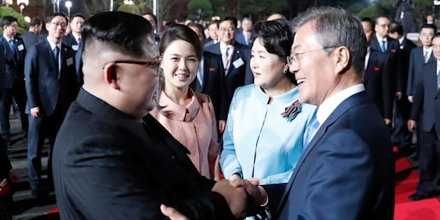 This picture taken on April 27, 2018 shows North Korea's leader Kim Jong Un (L) and South Korea's President Moon Jae-in (R) bidding farewell during a closing ceremony of the inter-Korean summit in the truce village of Panmunjom.