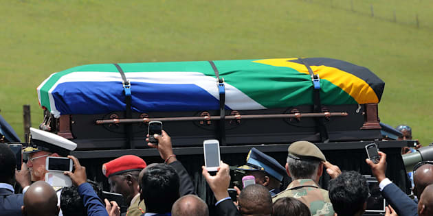 People take pictures as the coffin of South African former president Nelson Mandela is carried on a gun carrier for a traditional burial during his funeral in Qunu on December 15, 2013.