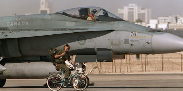 A Canadian CF-18 pilot prepares to take off, as a member of the ground crew pedals his bicycle past the jet in Qatar, on Jan. 20, 1991 during the Gulf War.