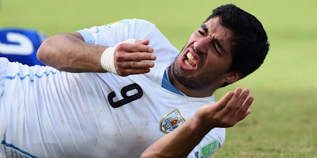 ワールドカップ・ブラジル大会で、試合中にイタリア選手に噛み付いたにもかかわらず、自身が痛がる仕草を見せるウルグアイのスアレス=2014年6月24日、ブラジル・ナタール