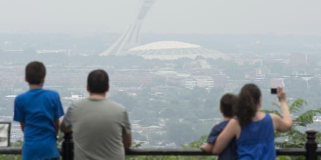 Des touristes photographient le Stade olympique à l'été 2013, un jour de smog.