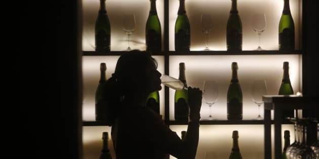 A woman poses with a glass of wine at a tapas bar in Mumbai March 9, 2013.
