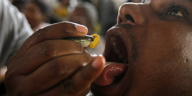 A man prepares to swallow a live fish that has been dipped in homemade medicine as people crowd for their turn in a camp in Hyderabad.