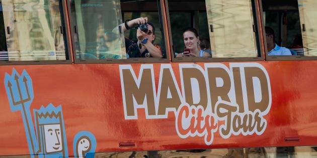 Unos turistas toman fotos de Madrid desde el autobús turístico que recorre el centro de la ciudad.
