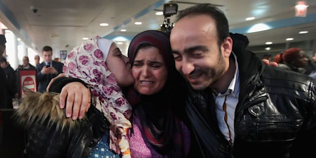Syrian refugee Baraa Hajj Khalaf, left, and her husband, Abulmajeed, are greeted by her mother, Fattuom, after a second-attempt flight from Turkey to Chicago on Feb. 7.
